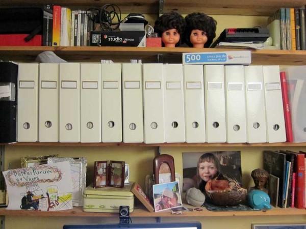 Eftersom jag gillar diskbänksrealism fotar jag här, utan krusiduller bokhyllan ovanför mitt arbetsbord. Inget för inredningsbloggen direkt.